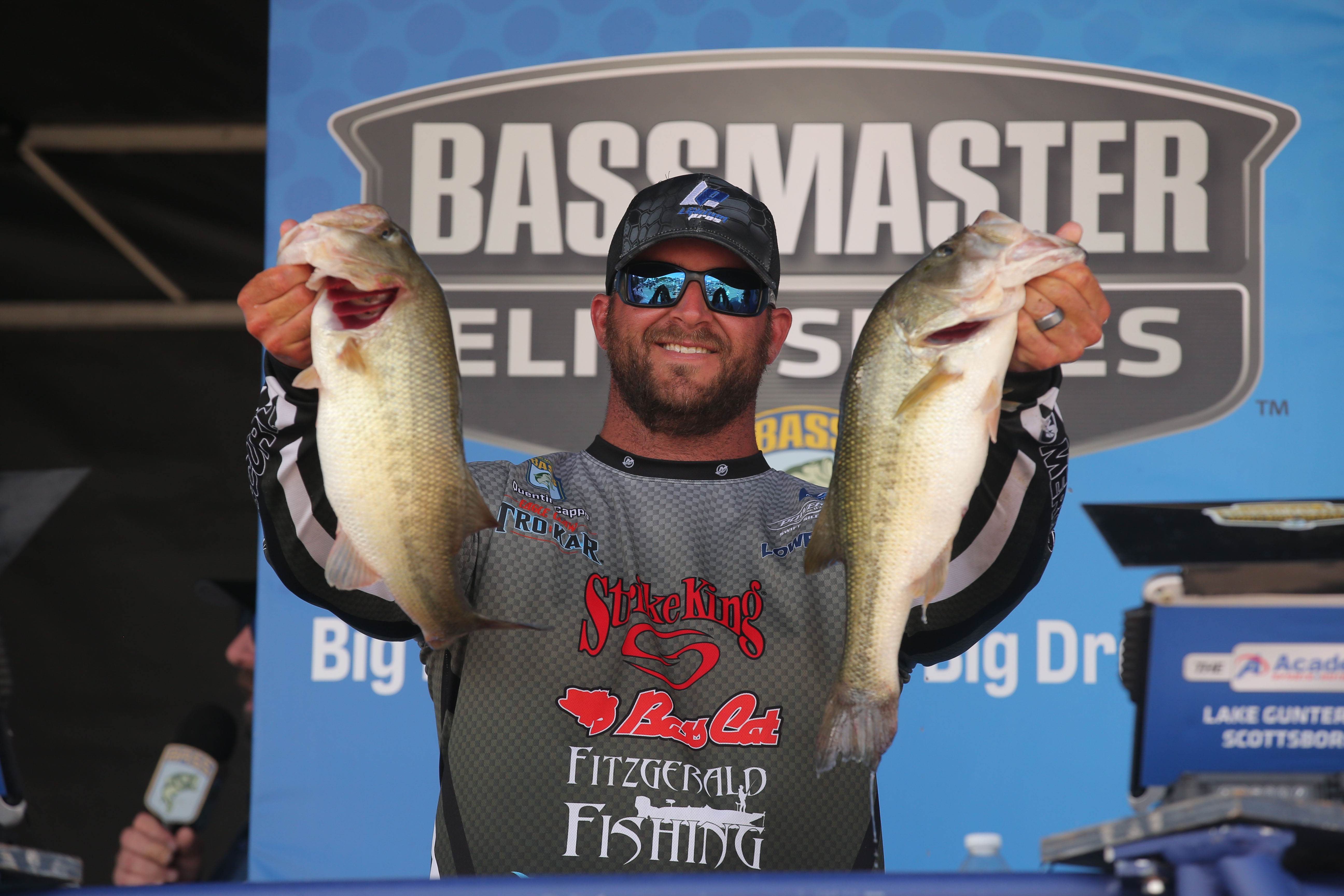 Bass Pro holding up 2 trophy fish